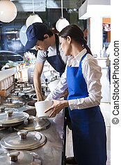 Male And Female Workers Preparing Ice Creams At Counter
