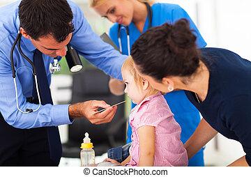 male doctor examining little girl