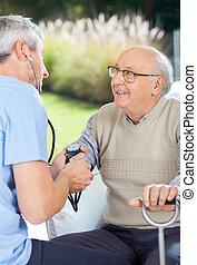 Male Doctor Measuring Blood Pressure Of Elderly Man