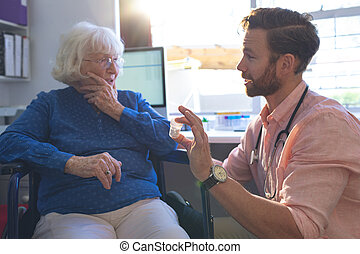Male doctor talking with senior female patient in clinic