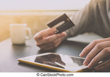 Male hands holding credit card and using Tablet with a cup of coffee on the table, soft focus, flare sun light, Online shopping concept.