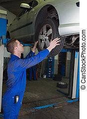 Male mechanic examining car tire