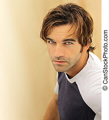 Portrait of a casual good looking male model with striking blue eyes