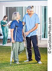 Male Nurse Assisting Senior Woman To Use Crutches