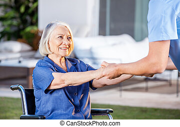 Male Nurse Helping Senior Woman To Get Up From Wheelchair