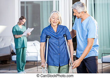 Male Nurse Helping Senior Woman To Use Crutches