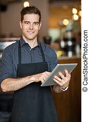 Male Owner Holding Digital Tablet In Cafeteria