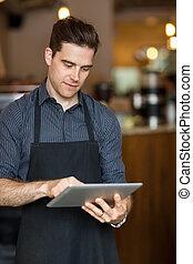 Male Owner Using Digital Tablet