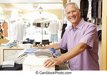 Male Sales Assistant At Checkout Of Clothing Store