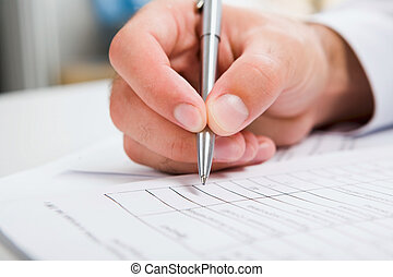 Male hand is writing in business document lying on the table