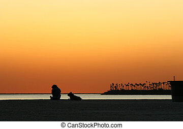 Man and dog on beach at sunset