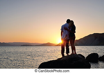 Man and woman standing in an embrace and watch the sunset
