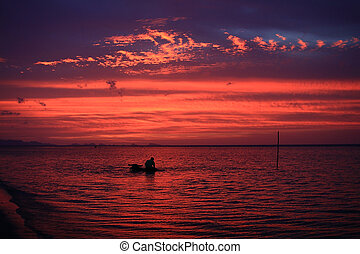 Man bathing buffalo in sunset sea at Samui island, Thailand