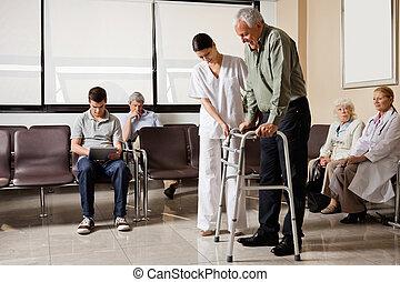 Man Being Helped By Nurse To Walk Zimmer Frame