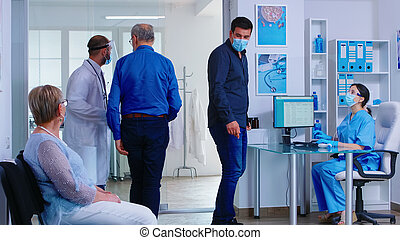 Man discussing with nurse at hospital reception