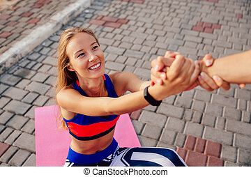 Man helps a sportswoman to get up outdoors