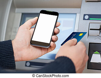 man holding phone and a credit card at an ATM