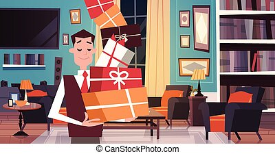 Man Holding Pile Of Gift Boxes Walking Through Living Room At Home Holiday Presents Concept