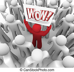 A satisfied customer holds a Wow sign in a crowd to illustrate suprise and satisfaction