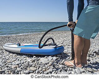 Man inflating stand up paddle board