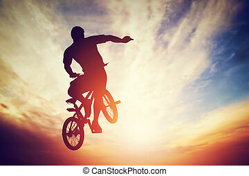 Man jumping on bmx bike performing a trick against sunset sky