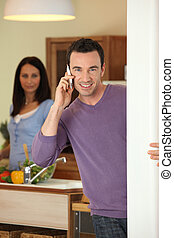 Man making a call whilst wife prepares meal