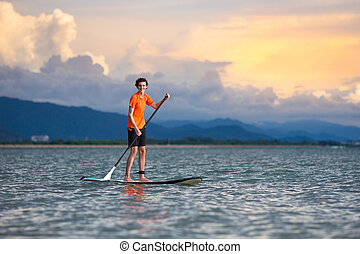 Man on stand up paddle. Water and beach sport