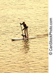 man paddleboarding with dog