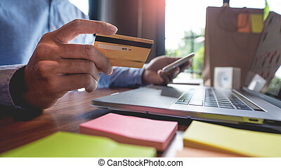 Man paying with credit card and entering security code for online shopping making a payment or purchasing goods on the internet with laptop computer, online shopping concept