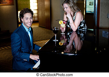 Man playing piano and entertaining his companion holding cocktail