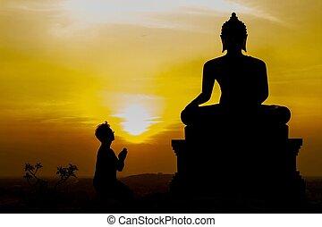 Man Praying To Statue Of Buddha at temple