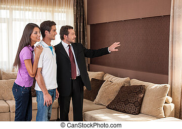 man real estate agent showing couple new house. male agent showing view from window on city