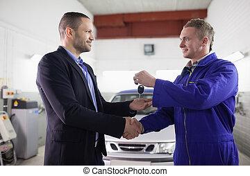 Man receiving car key while shaking hand to a mechanic