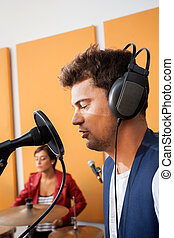 Man Singing With Female Drummer In Background