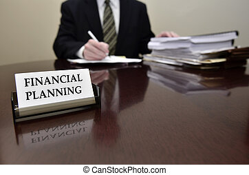 Man sitting at desk holding pen papers with business card for Financial Planning