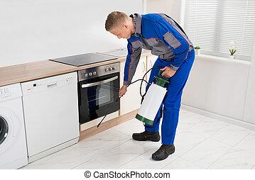 Man Spraying Pesticide In Kitchen Room