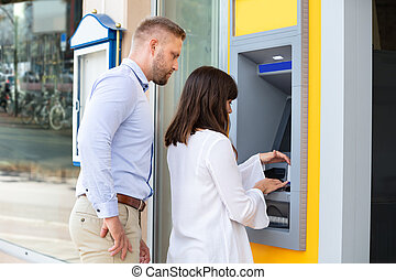 Man Spying For PIN Code While Woman Using An ATM