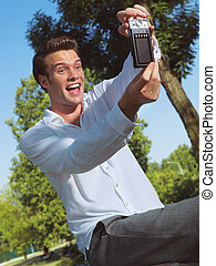 man taking photo with cellphone in park