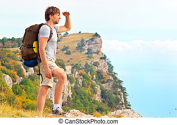 Man Traveler with backpack looking forward outdoor with hands up mountains on background Freedom and Healthy Lifestyle Hiking concept