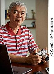 Man uploading photos from camera on laptop