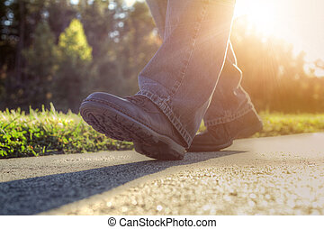Close up of a man walking on road.