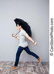 Man walking with umbrella in studio