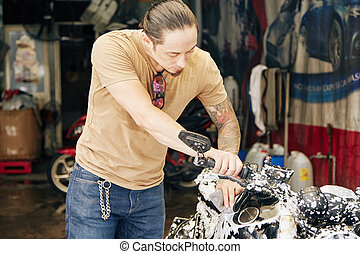 Man washing motorcycle with cleaning foam