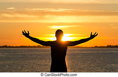 Man with arms wide open on the beach at sunrise
