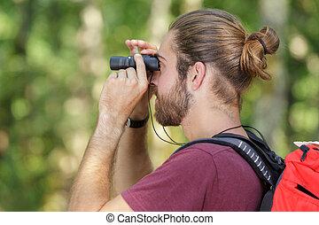 man with binoculars in nature
