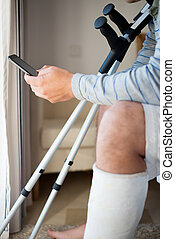 Young Man with Injury dialing the phone
