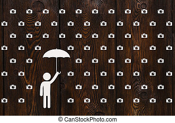 Man with umbrella standing in rain of cameras, abstract concept