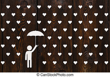 Man with umbrella standing in rain of hearts, abstract concept