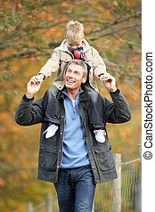 Man With Young Son On Shoulders Autumn Park