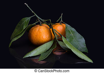 mandarin or tangerine with leaves and branches on a marble table - low key